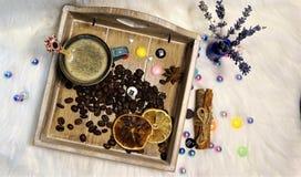 有杯的木盘子热的咖啡用肉桂条 咖啡豆、肉桂条、八角和干桔子 库存照片