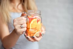 有杯的特写镜头愉快的妇女与秸杆的新鲜的夏天柠檬水 白种人少女户内20-25岁 免版税库存图片