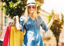 有杯的白肤金发的妇女在购物以后的汁液 免版税库存照片