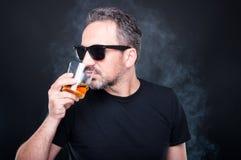 有杯的确信的年轻人威士忌酒 免版税图库摄影