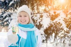 有杯的美丽的可爱的金发碧眼的女人香槟在她的手上庆祝新年 免版税图库摄影