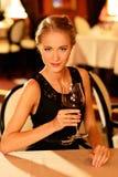 有杯的美丽的女孩红葡萄酒 库存照片