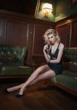 有杯的美丽的性感的公平的头发妇女酒坐沙发 一名妇女的画象有形成挑战的长的腿的 免版税图库摄影