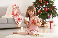 有杯的逗人喜爱的小女孩牛奶和曲奇饼在为圣诞节装饰的屋子里 免版税库存照片
