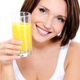 有杯的年轻微笑的妇女橙汁 库存图片