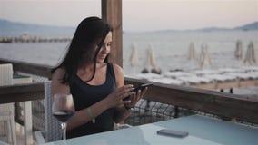 有杯的年轻浅黑肤色的男人使用她的片剂个人计算机的红葡萄酒,当坐在咖啡馆由海在日落时 影视素材