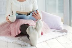 有杯茶休息格子花呢披肩的,与白色袜子的脚妇女 库存照片