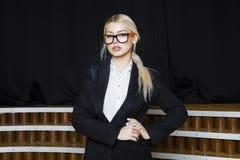 有松的嘴唇的美丽的白肤金发的女实业家在橙色玻璃和衣服的顶楼办公室 到达天空的企业概念金黄回归键所有权 库存照片