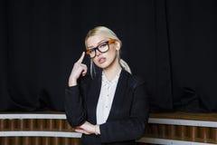 有松的嘴唇的美丽的白肤金发的女实业家在橙色玻璃和衣服的顶楼办公室 到达天空的企业概念金黄回归键所有权 免版税图库摄影