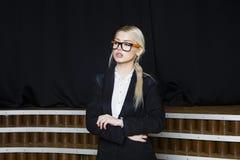 有松的嘴唇的美丽的白肤金发的女实业家在橙色玻璃和衣服的顶楼办公室 到达天空的企业概念金黄回归键所有权 免版税库存图片