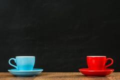 有板材安排的蓝色和红色咖啡杯 库存图片