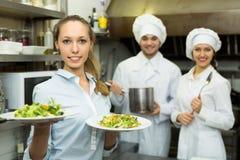 有板材的女服务员在厨房 免版税库存图片
