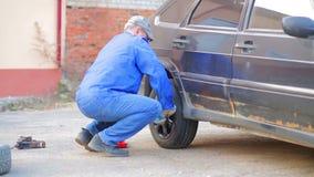 有板钳的男性汽车机械师巩固一个车轮 股票视频
