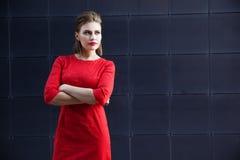有构成的美丽的女孩在一件红色礼服在一个现代城市 库存图片