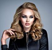 有构成的美丽的白肤金发的女孩在样式发烟性眼睛 免版税库存照片