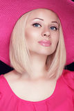 有构成的美丽的白肤金发的妇女,摆在桃红色h的微笑的女孩 免版税库存照片