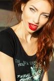 有构成的美丽的年轻性感的女孩与诱惑大红色嘴唇和长的头发在一个晴朗的夏日坐街道 库存图片