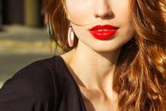 有构成的美丽的年轻性感的女孩与诱惑大红色嘴唇和长的头发在一个晴朗的夏日坐街道 免版税库存图片