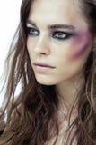 有构成的年轻秀丽妇女喜欢在面孔的发亮光物体 免版税库存图片