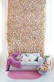 有枕头和桃红色盖子的一个轻的沙发,对被锯的木头墙壁  库存照片