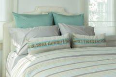有枕头和台灯的舒适卧室在床头柜上 免版税库存照片
