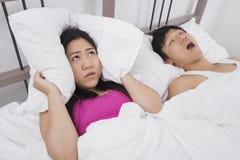 有枕头的沮丧的妇女覆盖物耳朵,当打鼾在床上时的人 免版税库存图片