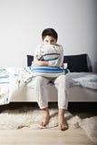 有枕头的醒的男孩 库存图片