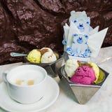 有果子冰淇凌和一杯咖啡的两种金属碗 免版税库存照片