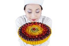 有果子蛋糕的少妇厨师 免版税库存照片