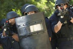 有枪和盾的警察 免版税图库摄影