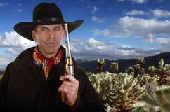 有枪感人的帽子的牛仔在cholla庭院里 图库摄影