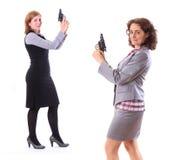 有枪的两个年轻秀丽女商人 免版税库存图片