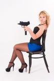 有枪的俏丽的女孩在椅子 库存照片