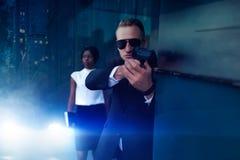 有枪的保镖保护女性VIP客户 免版税图库摄影