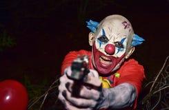 有枪的可怕邪恶的小丑 图库摄影