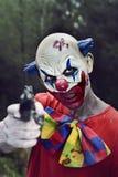 有枪的可怕邪恶的小丑 免版税库存照片