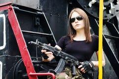 有枪的女孩坐蒸汽机车的踏板 免版税库存照片