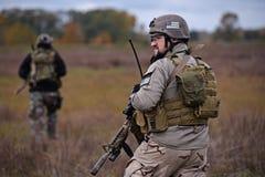 有枪的战士在盔甲和身体装甲 库存照片