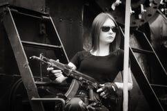 有枪的深色头发的女孩 库存图片
