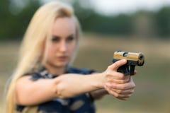 有枪的美丽的妇女别动队员 免版税库存照片