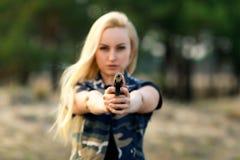 有枪的美丽的妇女别动队员 免版税库存图片