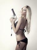 有枪的美丽的白肤金发的妇女 免版税库存图片