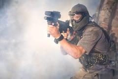 有枪的迷彩漆弹运动射击者 免版税库存照片