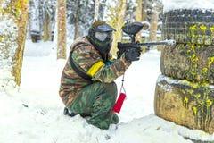 有枪的迷彩漆弹运动球员在雪的轮胎后 免版税图库摄影