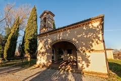 有柏的小13世纪农村教会 免版税库存图片