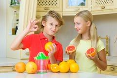 有柑橘的孩子 显示好接近的女孩的男孩 免版税库存照片
