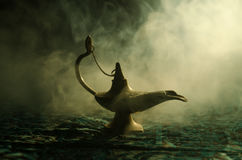 有柔光白色烟的,黑暗的背景古色古香的阿拉丁阿拉伯之夜灵魔样式油灯 愿望概念灯  定调子 库存照片