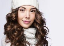 有柔和的构成、卷毛和微笑的美丽的女孩在白色编织帽子 温暖的冬天图象 秀丽表面 图库摄影