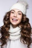 有柔和的构成、卷毛和微笑的美丽的女孩在白色编织帽子 温暖的冬天图象 秀丽表面 免版税图库摄影