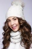 有柔和的构成、卷毛和微笑的美丽的女孩在白色编织帽子 温暖的冬天图象 秀丽表面 免版税库存图片